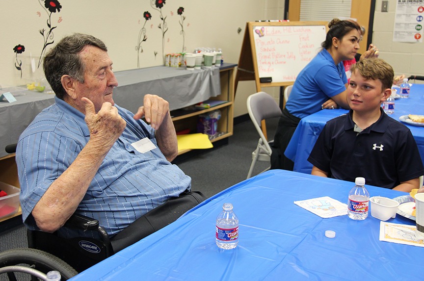 Eden Hill resident John Underwood visits with Thomas Schnabel, a student at Lamar Elementary, during a luncheon held for the residents on May 1 at the school.
