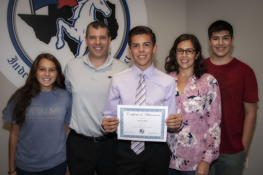 CAPTION: Jeremy Alkire (center) is pictured with his family at the October 16, 2019, NBISD Board meeting after being recognized for being named a 2019 National Merit Commended Student from New Braunfels High School.